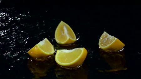 sıçramasına : Orange falls into the water and breaks up into four parts. Black background. Slow motion