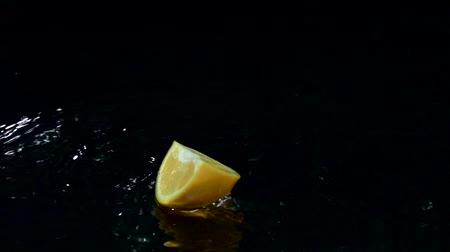 sputter : Slice of orange falls into the water. Black background. Slow motion Stock Footage