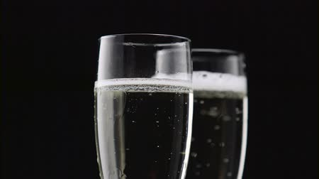 hiss : Filled with two glasses of champagne with white bubbles on a black background. Close up