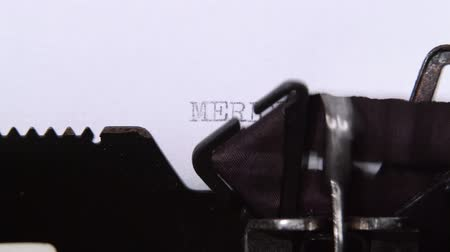 realization : Man is typing a letter on the typewriter of a merry christmas. Close up