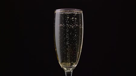 hiss : Glass of champagne with a rotating bubbles inside. Black background. Close up
