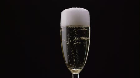 ünnepies : Glass of champagne with a rotating bubbles inside. Black background. Close up