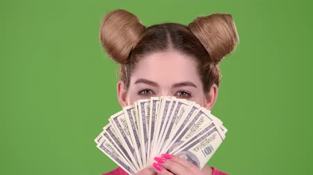 жадный : Girl holds paper bills and winks. Green screen. Close up Стоковые видеозаписи