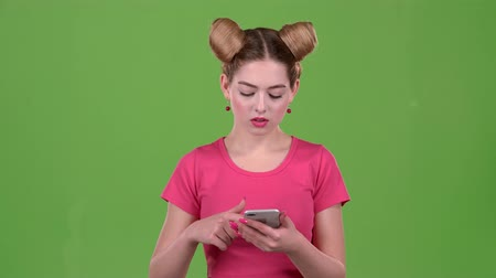 telefon : Girl looks at the phone and is surprised at what she saw. Green screen. Slow motion