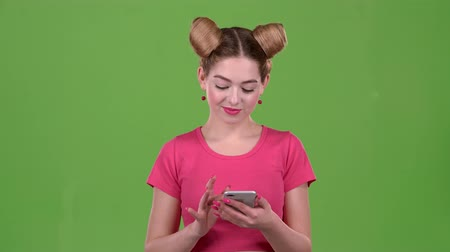 telefon : Girl looks at the phone and is surprised at what she saw, shows a thumbs up. Green screen. Slow motion