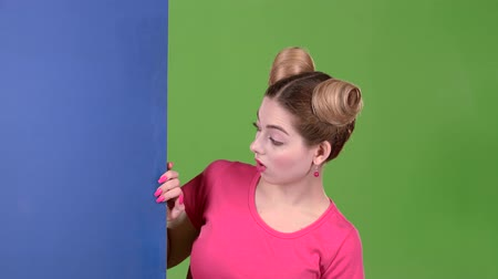 cem : Girl peeks out from behind a blue board and shows a ok. Green screen. Slow motion Vídeos