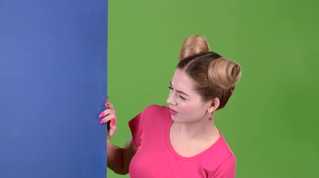 cem : Teenager peeks out from behind a blue board and shows a thumbs down. Green screen. Slow motion Vídeos
