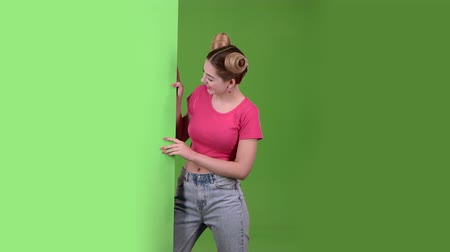 cem : Girl peeks out from behind a green board and shows a ok. Green screen. Slow motion