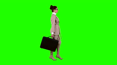 goes : Girl with cases in her hands goes to work. Green screen. Side view
