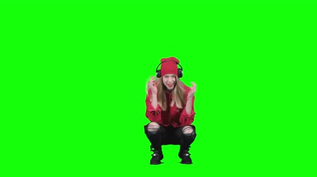 haunches : Teen girl sitting on her haunches and listening to music on headphones. Green screen