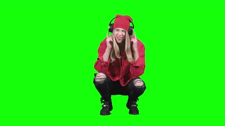 haunches : Girl sitting on her haunches and listening to music on headphones. Green screen