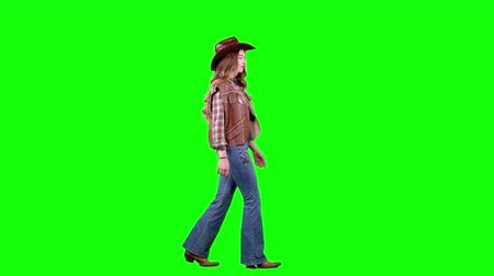 hat : Girl is walking along the street dressed as a cowboy. Green screen. Side view