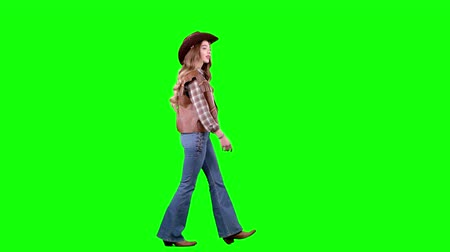 hat : Cowboy girl in a waistcoat and hat walks along the road and winks. Green screen. Side view
