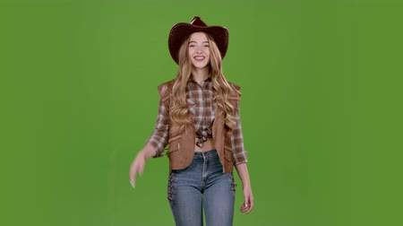 hat : Girl is walking along the street dressed as a cowboy. Green screen