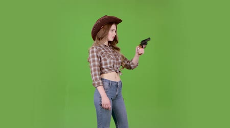 villain : Cowgirl in a hat, cowboy boots and a vest shoots a revolver. Green screen Stock Footage