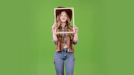 hat : Girl is holding a wooden frame and posing as a cowboy. Green screen