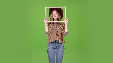 hat : Cowgirl is holding a wooden frame and posing as a cowboy. Green screen