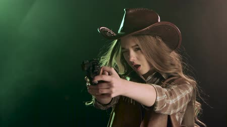 villain : Cowgirl holds a revolver in her hands and aiming at the villain. Black smoke background. Slow motion