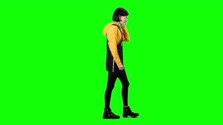 bok : Girl is talking on the phone walking down the street. Green screen. Side view