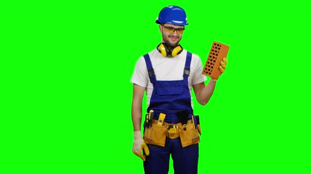 шпатель : Engineer holds a brick in his hand and shows a thumbs up. Green screen