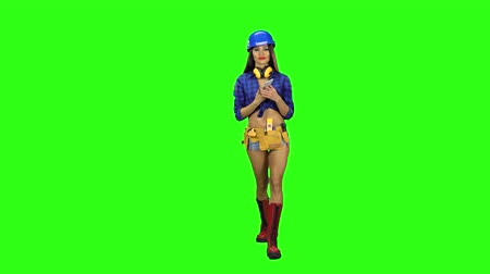 chroma key background : Girl in shorts and a helmet is talking on the phone on a green background