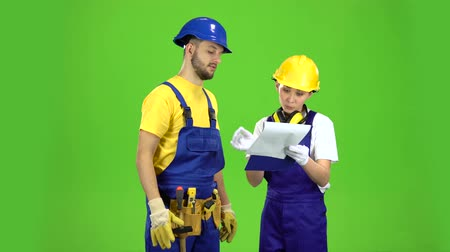 оттенки : Designer girl shows a sketch of a building to a builder. Green screen Стоковые видеозаписи