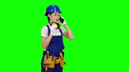 hat : Engineer is standing and talking on the phone. Green screen