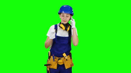 hat : Builder girl is standing and talking on the phone. Green screen