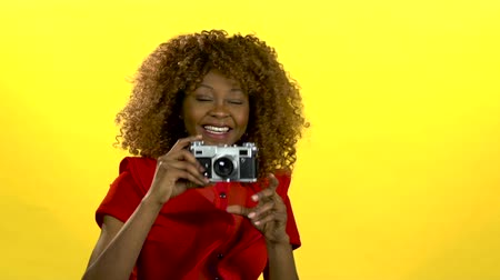 conquest : Afro american photographer holds a camera in her hands . Yellow background. Slow motion