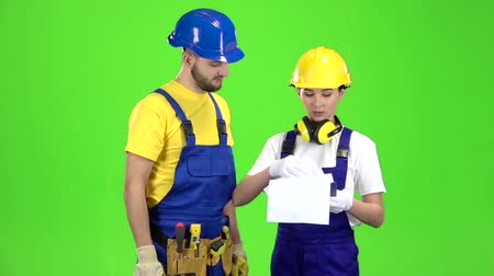 оттенки : Designer girl shows a sketch of a building to a builder. Green screen. Slow motion