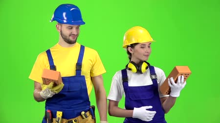 шпатель : Pair of builders holding a brick in their hands and showing their fingers up. Green screen. Slow motion