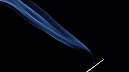 ethereal : Close up of burning incense sticks with smoke over black background Stock Footage