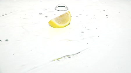 ostatky : Quarter of a lemon drops into the water and remains there. White background. Slow motion