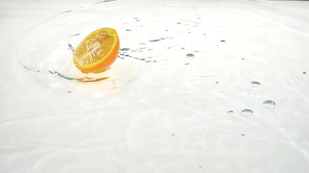 цитрусовые : Half a orangedrops into the water. White background. Slow motion Стоковые видеозаписи