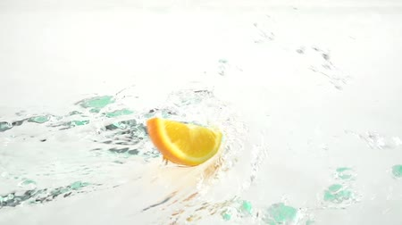 ostatky : Quarter of a orange drops into the water and remains there. White background. Slow motion Dostupné videozáznamy