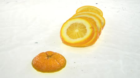 vitamin water : Orange falls into the water and flakes to the lobules. White background. Slow motion Stock Footage