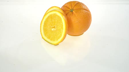 mosás : Slice of orange falls into the water . White background. Slow motion