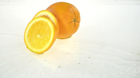 suco : Slice of orange falls into the water . White background. Slow motion