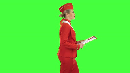 attendant : Woman steps along with a red folder in her hands. Green screen. Side view