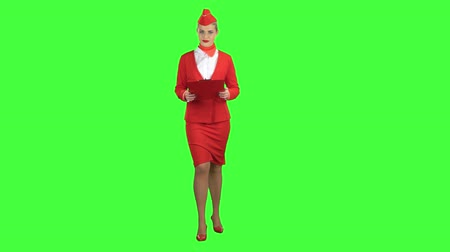 crew : Woman steps along with a red folder in her hands. Green screen
