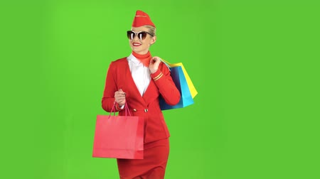 экипаж : Girl in sunglassesis is coming with shopping bags. Green screen