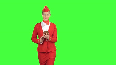 goes : Woman steps with the phone and writes a message . Green screen