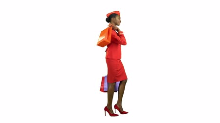 comes : Afro american girl comes with shopping bags shes a flight attendant. Alpha channel. Side view