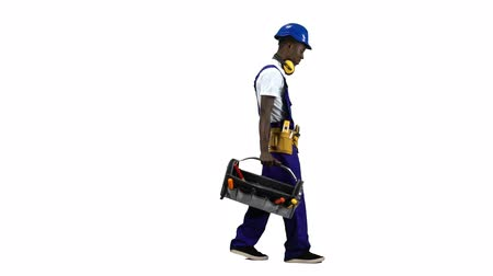 alicate : African American construction worker goes to work with a suitcase with tools . Alpha channel. Side view