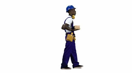 comes : African American builder goes to work with wooden planks in his hands. Alpha channel. Side view