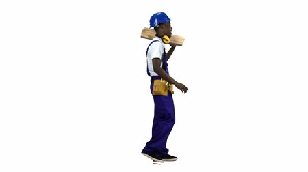 comes : Builder african american goes to work with wooden planks in his hands. Alpha channel. Side view Stock Footage