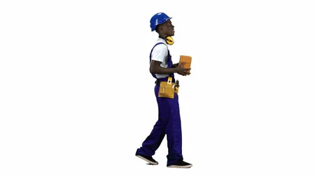 bastante : African american builder in a helmet carries three bricks in his hand . Alpha channel. Side view