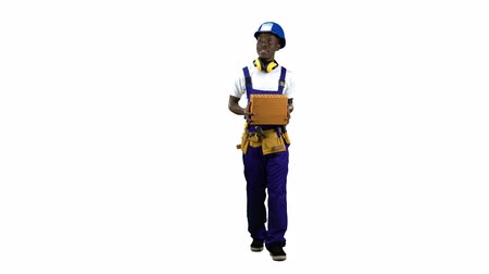 bastante : African american builder in a helmet carries three bricks in his hand . Alpha channel Stock Footage