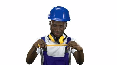 ruletka : Builder african american takes measurements with a yellow tape measure. Alpha channel Wideo