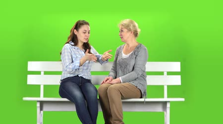 konuları : Mom and daughter are sitting on a bench. Green screen Stok Video